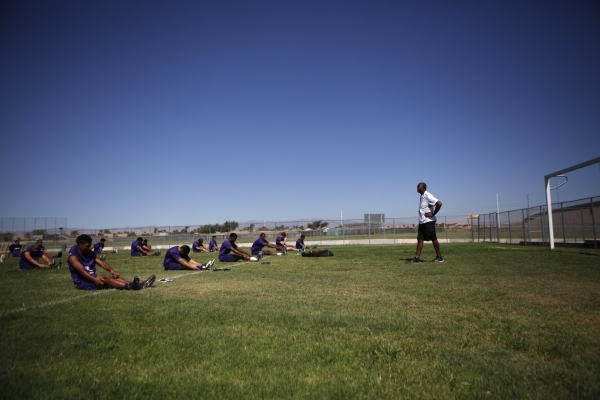 Randall Cunningham, Silverado High School head football coach, looks on at his players during a stretch exercise at Silverado High School in Las Vegas on Monday, August 10, 2015. Cunningham is a p ...