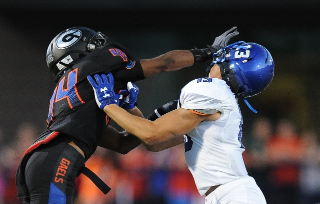Bishop Gorman defensive back Brendan Radley-Hiles (44) tussles with Chandler wide receiver Taj De Carriere (13) after a play in the first quarter of their high school football game at Bishop Gorma ...