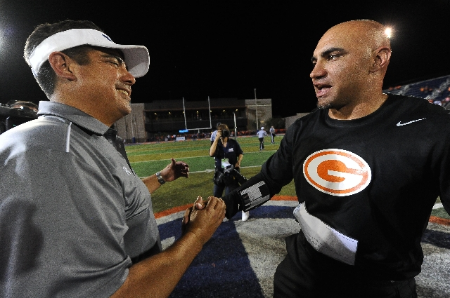 Bishop Gorman head coach Kenny Sanchez, right, and Chandler (Ariz.) head coach Shaun Aguano shake hands after the completion of their high school football game at Bishop Gorman High School in Las  ...