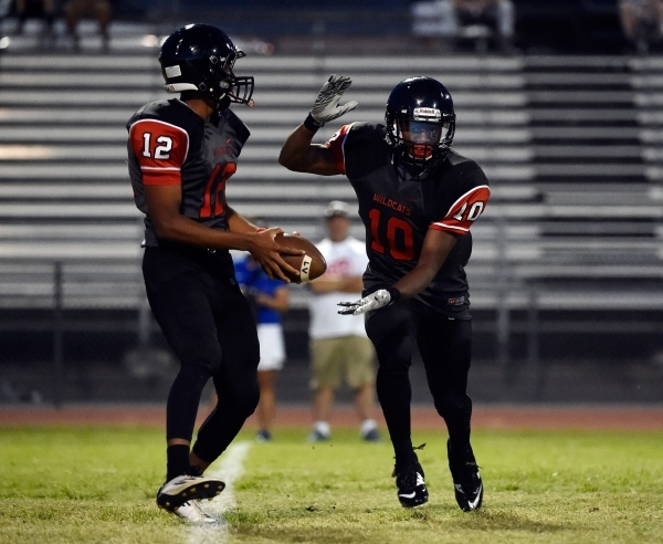 Las Vegas quarterback Zach Matlock (12) appears to hand off the ball to Elijah Hicks during a high school football game at Las Vegas High School against Green Valley on Friday, Sept. 4, 2015. (Dav ...