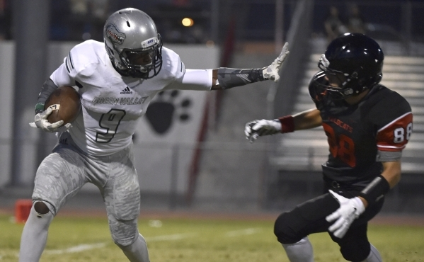 Green Valley's Nahzi Salih (9) holds Las Vegas' Cody Kludasch on a punt return during the first half of a high school football game at Las Vegas High School on Friday, Sept. 4, 2015. ( ...