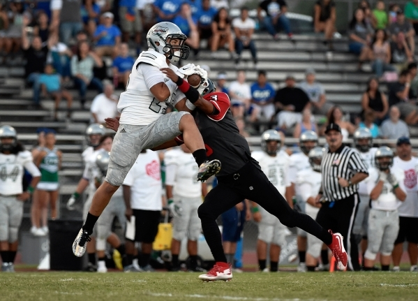 Green Valley's Christian Mayberry, left, catches the ball over Las Vegas' Zachary Loveland during a high school football game at Las Vegas High School on Friday, Sept. 4, 2015. (David  ...
