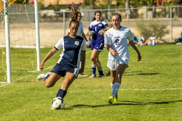 Katherine Ballou (6) of the Foothill Falcons passes the ball to a teammate as Brynna McGinnis of the Silverado Skyhawks looks on during a soccer match at Silverado High School in Las Vegas on Tues ...