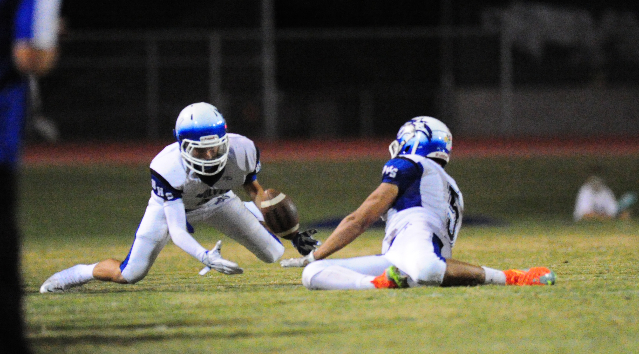 Basic Wolves safety Austin Owens, left, recovers a Green Valley fumble in the first quarter of their prep football game at Green Valley High School in Henderson Friday, Oct. 9, 2015. Josh Holmberg ...
