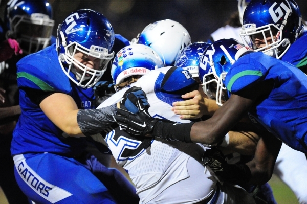 Basic Wolves running back Sean White, middle is brought down by Green Valley Gators linebacker Preston Howard, left, and Green Valley Gators safety Marquez Powell, right, in the fourth quarter of  ...