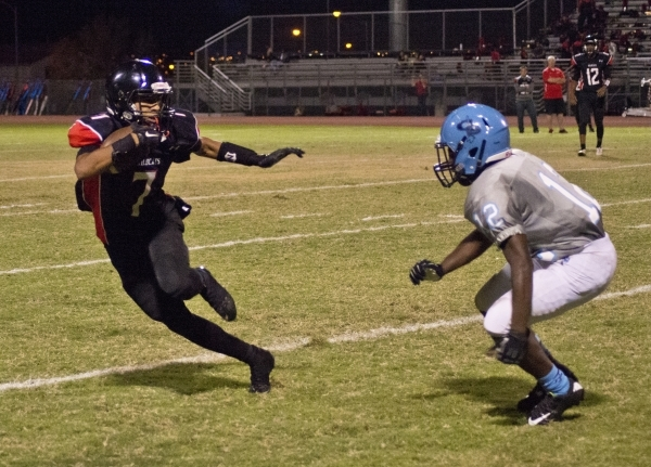Las Vegas' Raul Perez (7) attempts to work his way around Canyon Springs' Devin Allen-Tucker (12) during their prep football game at Las Vegas High School on Friday, Oct. 16, 2015. Las ...
