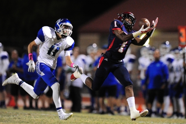 Coronado Cougars wide receiver Da Qu'an Davis (1) catches a pass for a first down as Green Valley Gators safety Ty Rivera defends in the first half of their prep football game at Coronado Hi ...