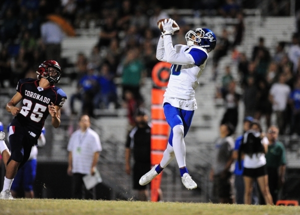 Green Valley Gators wide receiver Isiah Macklin catches a touchdown pass in front of Coronado Cougars safety Tyrus Silva (25) in the first half of their prep football game at Coronado High School  ...