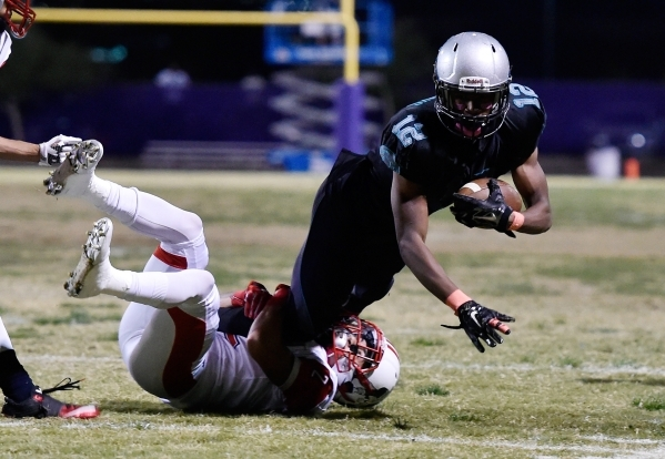 Silverado's Devion Clayton (12) dives for extra yardage as Liberty's Ethan Dedeaux pulls him down during the first half of a high school football game at Silverado High School on Frida ...