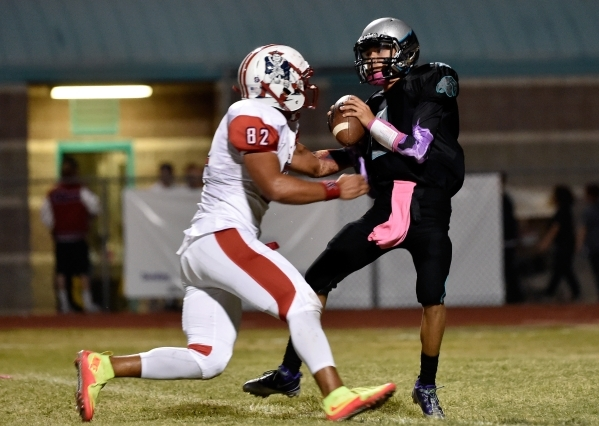 Silverado quarterback Christian Baltodano is under pressure from Liberty's Cyrius Vea during the first half of a high school football game at Silverado High School on Friday, Oct. 23, 2015.  ...