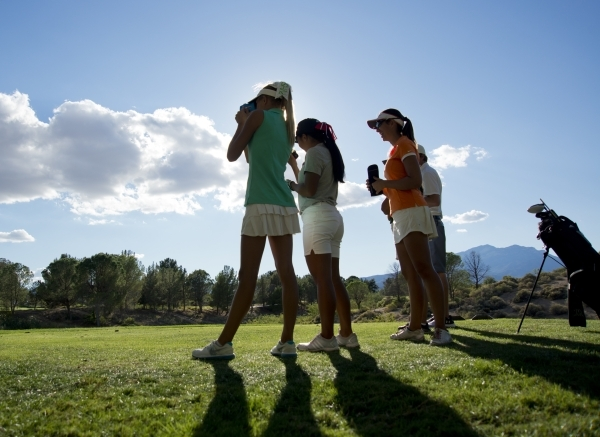 Annick Haczkiewicz of Palo Verde High School, center, measures the distance to the hole during the girls state championship golf tournament at the Primm Valley Golf Club in Nipton, Calif. on Thurs ...