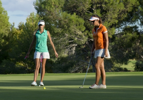 Annick Haczkiewicz, left, and Hunter Pate wait for their turn to put during the girls state championship golf tournament at the Primm Valley Golf Club in Nipton, Calif. on Thursday, Oct. 22, 2015. ...