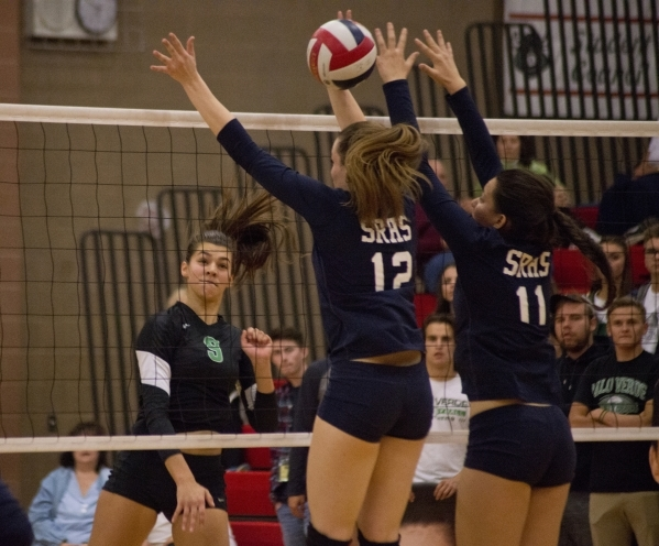 Palo Verde's Kayla Kinney (9) hits the ball through the block of Shadow Ridge's Rachel Chambers (12) and Kahea Nihipali (11) during the Sunset Region girls volleyball semifinal at Arbo ...