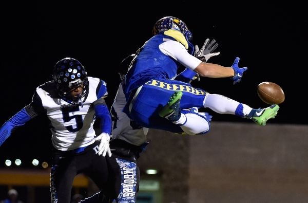 Moapa Valley's R.J. Hubert reached out to make a catch against Desert Pines' Eddie Heckard (5) and Dominique Washington during a high school football game at Moapa Valley High School i ...
