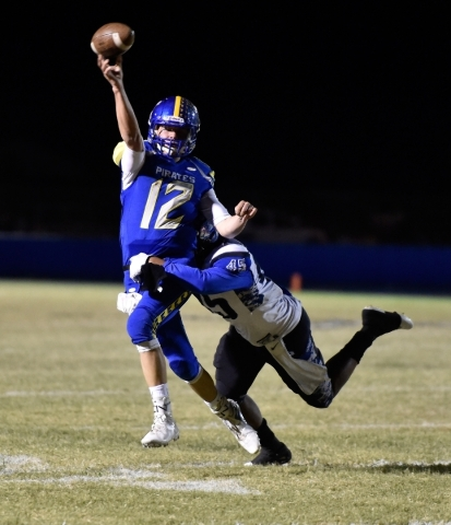 Moapa Valley quarterback Nate Cox passes the ball under pressure from Desert Pines' Jalen Graves during a high school football game at Moapa Valley High School in Overton on Friday, Nov. 6,  ...