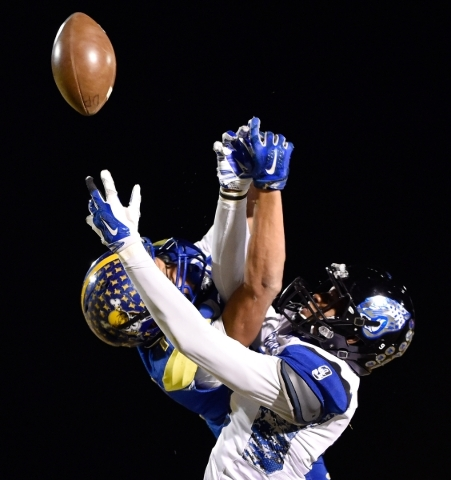 Moapa Valley's Trystin Deal makes a catch against Desert Pines' Eddie Heckard (5) and Andrew Gray during a high school football game at Moapa Valley High School in Overton on Friday, N ...