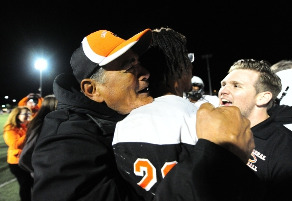 Chaparral head coach Paul Nihipali, left, hugs running back Richard Nelson after they upset Faith Lutheran 21-20 in their I-A state quarterfinal football game at Faith Lutheran High School in Las  ...
