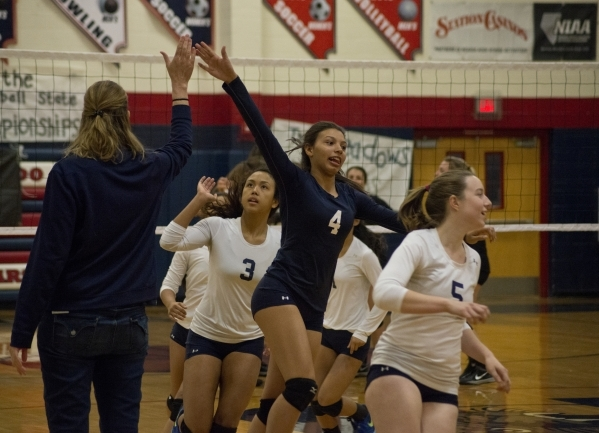 The Shadow Ridge High School girls volleyball team gives their coach, Karissa Guthrie, a high five before the Division I state semifinal match between Shadow Ridge and Bishop Manogue on Friday, No ...