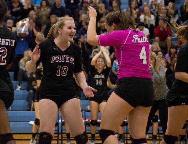 Faith Lutheran's Logan Van Reken (4) and Megan Kronschnabel (10) celebrate a point during the division I-A state volleyball final match between Faith Lutheran and Truckee at Foothill High Sc ...