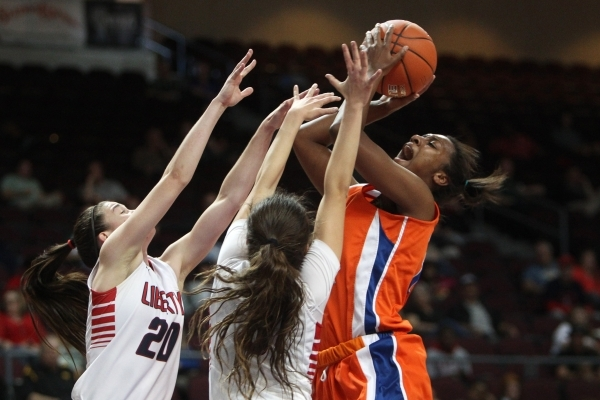 Bishop Gorman forward Madison Washington shoots over Liberty guards Kealy Brown, left, and CeCe Quintino during their Division I state semifinal game Thursday, Feb. 26, 2015, at the Orleans Arena. ...