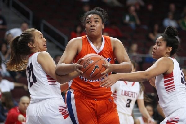 Bishop Gorman forward Raychel Stanley drives between Liberty guard Kaily Kaimikaua, left, and forward Paris Strawther during their Division I state semifinal game Thursday, Feb. 26, 2015, at the O ...