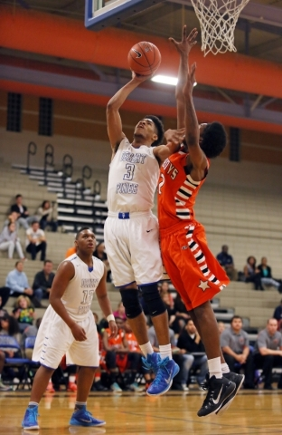 Desert Pinesí Trevon Abdullah, center, goes for a lay-up against Chaparral's Maharie Trotter during a basketball game at Desert Pines High School Wednesday, Jan. 21, 2015, in Las Vegas. C ...
