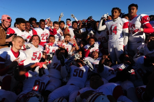 Liberty players hoist the Sunrise Region trophy after defeating Basic 62-22 during the NIAA Division 1 Sunrise Region Football Final prep football game at Basic High School in Henderson Saturday,  ...