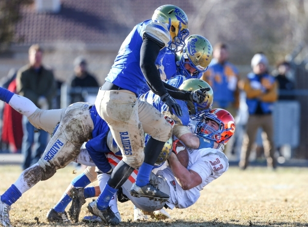 Bishop Gorman's Jonathan Shumaker gets tackled by a wave of Reed defenders in an NIAA Division I playoff game at Reed High School in Sparks, Nev., on Saturday, Nov. 28, 2015. Bishop Gorman w ...