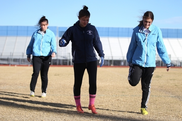 Centennial's Courtney Reeves, from left, Ashley Marshall and Cienna Mendez warm up during a girl's flag football practice at Centennial High School in Las Vegas Tuesday, Nov. 24, 2015. ...