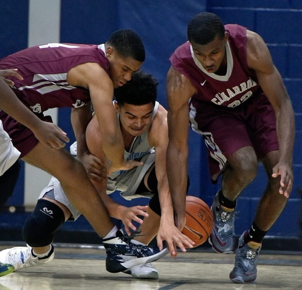 Cimarron-Memorial's Elijah Coleman, left, Canyon Springs' Joseph Haulcy, and Cimarron-Memorial's KeAnte Huddleston battle for a loose ball during a high school basketball game at ...