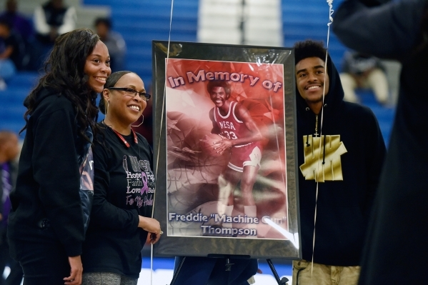 Family members from left, daughter, Aleah Thompson, wife, Bonita Thompson and son, AJ Thompson pose with a poster of the late Freddie Thompson during a ceremony at half-time at a high school baske ...
