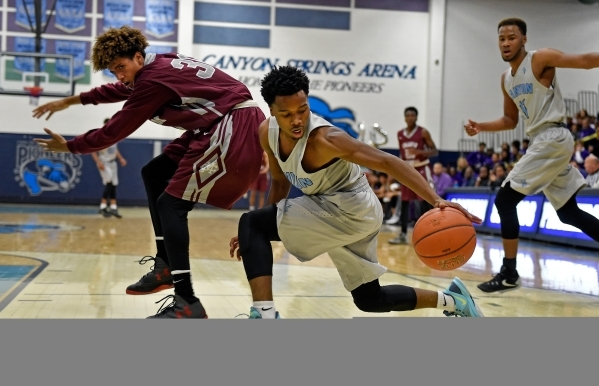 Canyon Springs' Laymon Jackson, right, grabs a loose ball from Cimarron-Memorial' Keiron Hatchett during a high school basketball game at Canyon Springs High School on Monday, Nov. 30, ...
