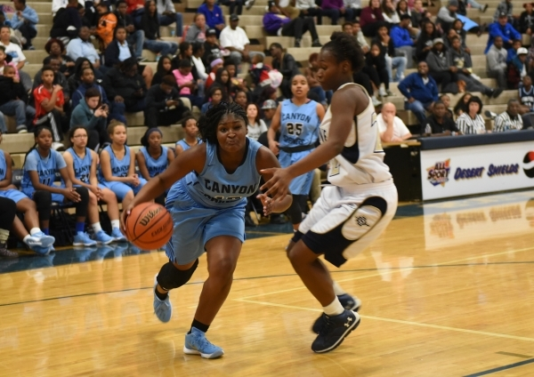 Canyon Springs Destini Hunter (10) drives by Cheyenne's Ejanae Coopwood (22) during their basketball game at the Cheyenne High School gym in North Las Vegas on Wednesday Dec. 2, 2015. Canyon ...
