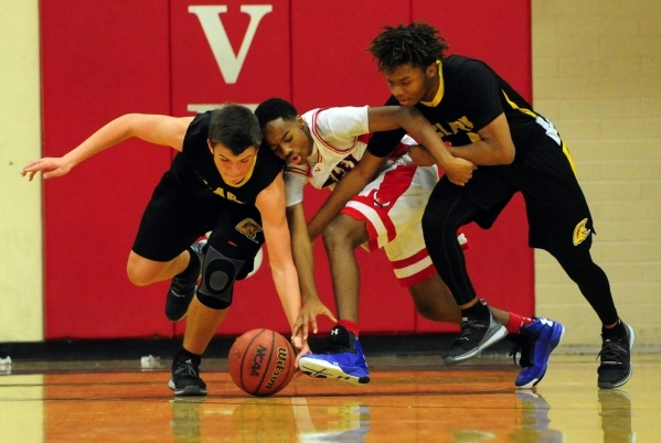 Clark Chargers guards James Bridges, left, and Keyshaun Webb (1) fight Valley Vikings guard Oscar Burns for a loose ball in the first quarter of their prep basketball game at Valley High School in ...