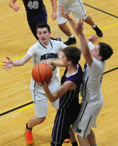 The Meadows School guards Jake Epstein (23) and Ethan Fridman (12) cover Spring Creek forward Dakota Larson (11) during their prep basketball game at Lake Mead Christian Academy in Henderson  Frid ...