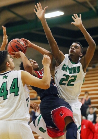 Libertyís David Bravo, center, gets tangled with Green Valley defense Ali Amhaz, left, and Deontae Tillman while going for a lay-up during a basketball game at Green Valley Tuesday, Dec. 8, 201 ...
