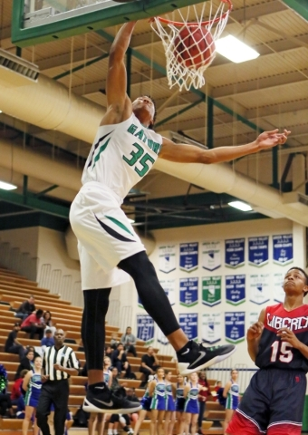Green Valleyís Isiah Macklin (cq), left, dunks near Libertyís Cameron Burist during a basketball game at Green Valley Tuesday, Dec. 8, 2015, in Henderson. Green Valley won the game, 84-65. R ...