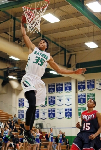 Green Valleyís Isiah Macklin (cq), left, goes up for a dunk near Libertyís Cameron Burist during a basketball game at Green Valley Tuesday, Dec. 8, 2015, in Henderson. Green Valley won the g ...