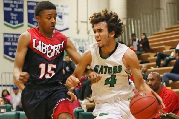 Green Valley's Xavier Jarvis, right, is defended by Liberty's Cameron Burist during a basketball game at Green Valley Tuesday, Dec. 8, 2015, in Henderson. Green Valley won the game, 84 ...