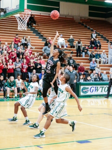 Desert Oasis freshman Ahmaya Smith (15) leaps up to make a basket while surrounded by Green Valley freshman Shelby Clark (11), and Green Valley junior Jamaica Lewis (12) during a basketball game a ...