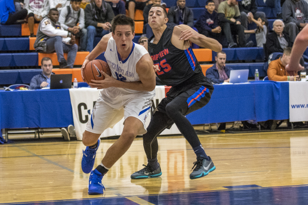 Bishop Gorman center Zach Collins (12) drives to the basket while being defended by Timpview (Utah) forward Gavin Baxter (25) during the first half at Bishop Gorman High School in Las Vegas on Wed ...