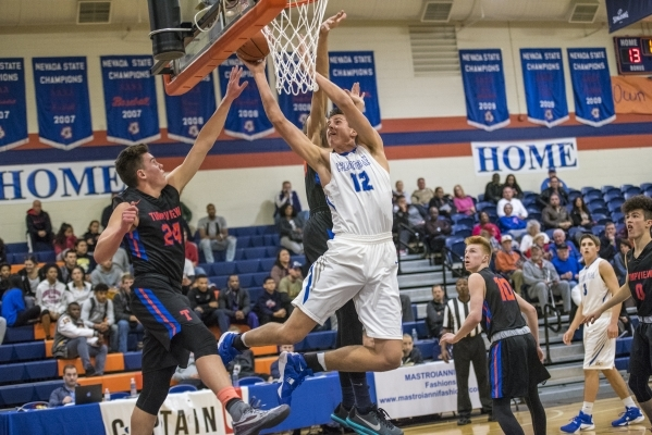 Bishop Gorman center Zach Collins (12) takes the ball to the basket while being defended by Timpview (Utah) forward Colson Santiago (24) during the first half at Bishop Gorman High School in Las V ...