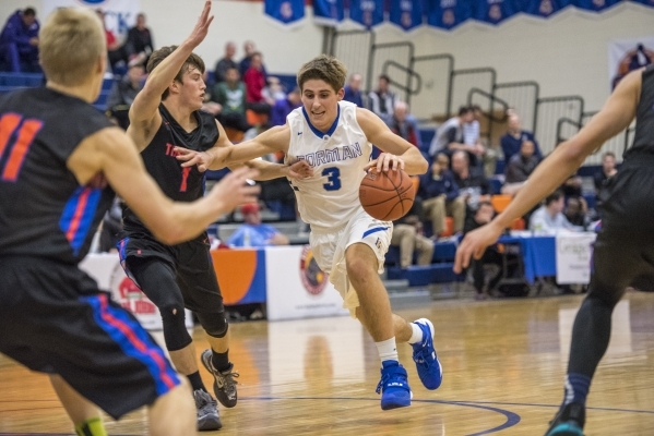 Bishop Gorman forward Byron Frohnen (3) drives to the basket while being defended by Timpview (Utah) guard Seth Santiago (1) during the first half at Bishop Gorman High School in Las Vegas on Wedn ...