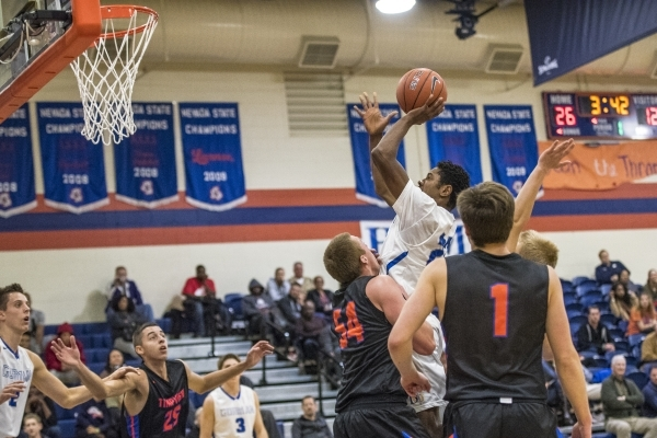 Bishop Gorman guard Christian Popoola Jr. (22) takes a shot while being defended by Timpview (Utah) center AJ Bollinger (54) during the first half at Bishop Gorman High School in Las Vegas on Wedn ...