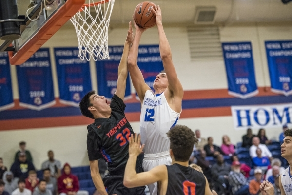 Bishop Gorman center Zach Collins (12) takes the ball to the basket while being defended by Timpview (Utah) center Caleb Roberts (32) during the first half at Bishop Gorman High School in Las Vega ...
