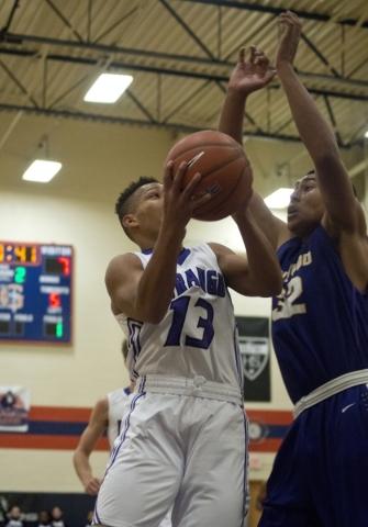 Durango High School's Demetrius Valdez (13) works the ball toward the net as Lynwood High School's Oscar Lopez (32) defends during the fourth annual Tarkanian Classic basketball tourna ...