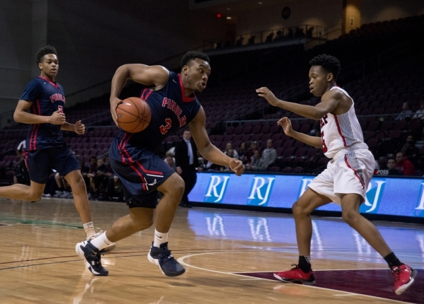 Findlay Prep's Carlos Johnson (3) advances the ball as Victory Prep's Michael Kimble (5) defends during the fourth annual Tarkanian Classic basketball tournament at the Orleans Arena i ...