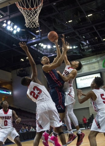Findlay Prep's Tristan Clark (12) takes the ball to the net while being defended by Victory Prep's Marvin Powell (21) and Quashi Philips (23) during the fourth annual Tarkanian Classic ...