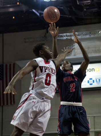 Findlay Prep's Shakwon Barrett (2) takes a shot at the net as Victory Prep's Antonio Terrell Jr. (0) defends during the fourth annual Tarkanian Classic basketball tournament at the Orl ...