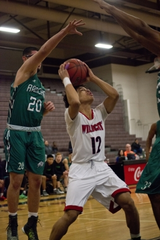 Las Vegas' Donovan Joyner (12) works the ball toward the net as Rancho's Michael Hernandez (20) defends during the Las Vegas Prep Championship basketball tournament at Las Vegas High S ...